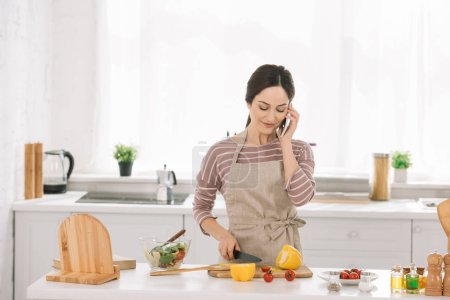 Photo for Smiling woman in apron cutting bell pepper while standing near kitchen table with vegetables and talking on smartphone - Royalty Free Image