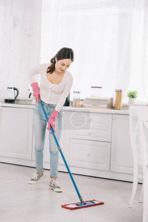 Photo pour Séduisant, jeune ménagère lave-linge dans la cuisine avec vadrouille - image libre de droit