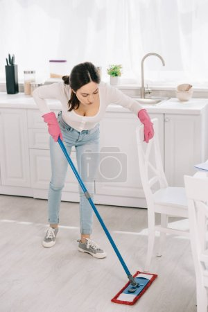 Photo pour Young housewife in blue jeans washing floor in kitchen with mop - image libre de droit