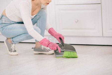 Photo pour Vue en coupe d'une jeune ménagère balayant le sol avec une brosse et une pelle - image libre de droit