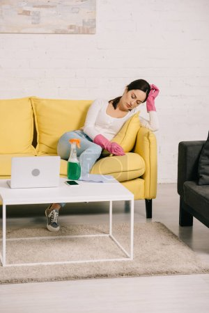 Photo pour Tired housewife sitting on yellow sofa with closed eyes near table with laptop and spray bottle - image libre de droit
