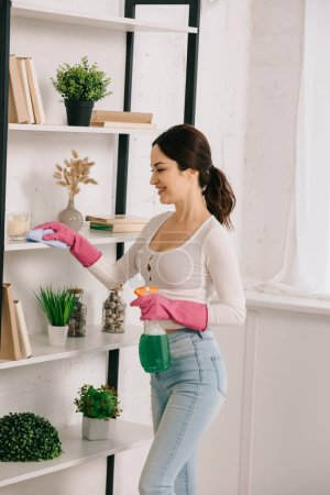 Photo pour Happy housewife cleaning rack with rag and holding spray bottle with detergent - image libre de droit