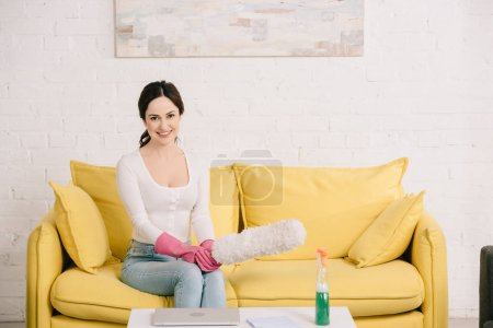 Foto de Happy housewife smiling at camera while sitting on yellow sofa and holding dusting brush - Imagen libre de derechos