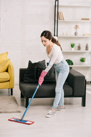 Photo pour Young housewife washing floor with mop near grey sofa - image libre de droit