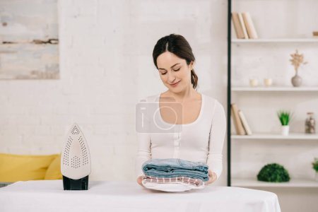 Photo for Young housewife holding ironed clothes and smiling while standing near ironing board - Royalty Free Image
