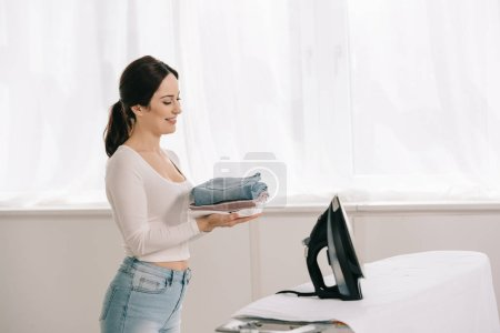 Photo for Happy housewife holding ironed clothes while standing near ironing board - Royalty Free Image