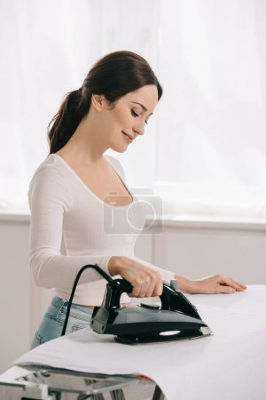 Photo for Attractive housewife smiling while ironing on ironing board - Royalty Free Image