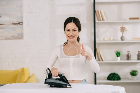 cheerful housewife ironing and showing thumb up while looking at camera