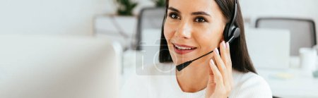 Photo pour Panoramic shot of cheerful broker touching headset while working in call center - image libre de droit