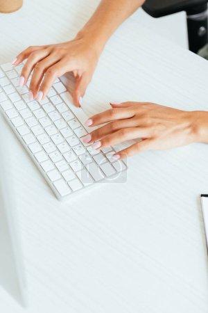 Photo pour Vue recadrée de la femme tapant sur le clavier d'ordinateur dans le bureau - image libre de droit