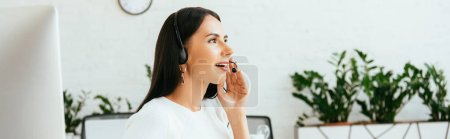 panoramic shot of smiling broker in headset talking in office