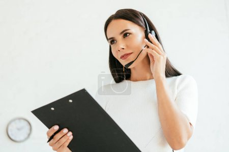 Photo for Attractive broker touching headset while holding clipboard in office - Royalty Free Image