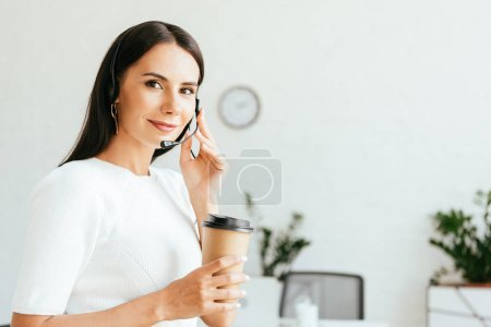Photo for Happy broker touching headset and holding paper cup - Royalty Free Image