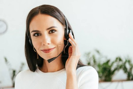 happy broker in headset looking at camera in office