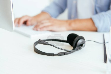 Photo pour Selective focus of black headset near operator in brokers agency typing in office - image libre de droit