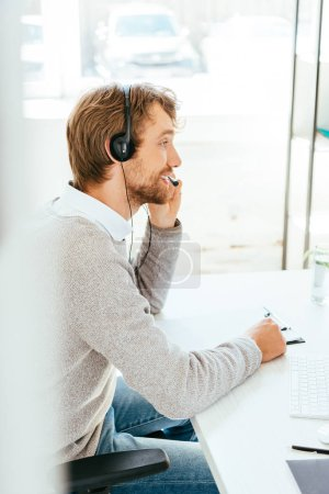 selective focus of happy bearded operator in brokers agency touching headset