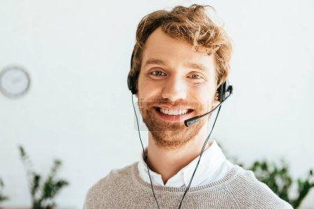 Photo pour Joyeux opérateur barbu dans l'agence de courtiers regardant la caméra - image libre de droit