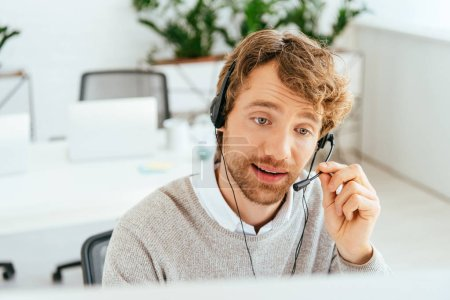 selective focus of handsome and bearded operator in brokers agency using headset
