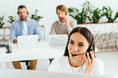 selective focus of broker touching headset near coworkers in office