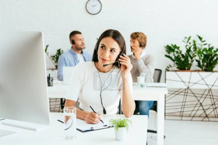Photo pour Selective focus of attractive broker with pen touching headset near coworkers - image libre de droit