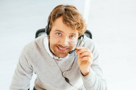 Photo pour Overhead view of cheerful bearded broker looking at camera in office - image libre de droit