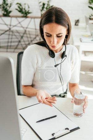Photo pour Courtier malade avec casque regardant pilule au bureau - image libre de droit
