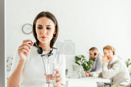 selective focus of sick broker holding pill and glass of water near coworkers in office