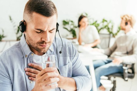 selective focus of sick broker holding glass of water in office