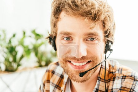 cheerful and bearded broker looking at camera in office