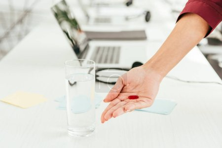 Photo for Cropped view of broker holding pill near glass of water and laptop in office - Royalty Free Image