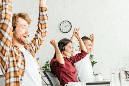 Photo pour Foyer sélectif des courtiers heureux avec les mains au-dessus des têtes dans le bureau - image libre de droit