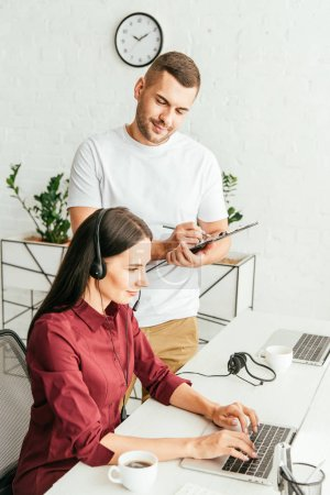 handsome broker holding clipboard while standing near woman in headset