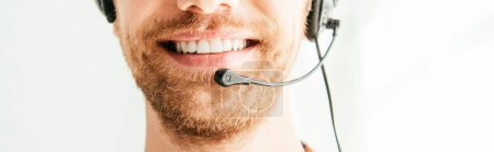 panoramic shot of bearded broker in headset smiling in office