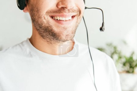 Photo pour Cropped view of positive broker in headset smiling in office - image libre de droit