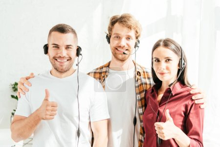 Photo for Happy brokers in headsets looking at camera and showing thumbs up - Royalty Free Image
