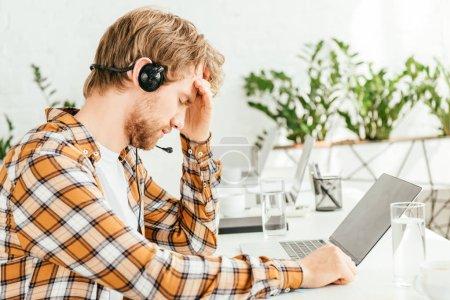 fatigué barbu courtier toucher la tête tout en étant assis près de l'ordinateur portable
