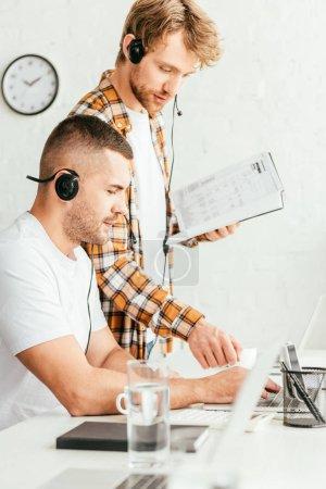 handsome broker standing with notebook near coworker in headset