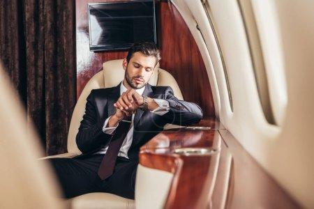 Photo pour Bel homme d'affaires en costume regardant montre-bracelet en avion privé - image libre de droit