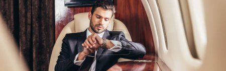 panoramic shot of handsome businessman in suit looking at wristwatch in private plane