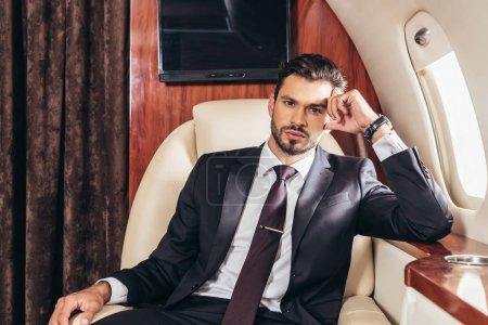 Photo pour Cher homme d'affaires en costume regardant la caméra dans un avion privé - image libre de droit