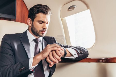 Photo pour Bel homme d'affaires en costume regardant montre-bracelet en avion privé - image libre de droit