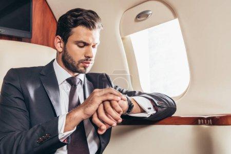 Photo pour Handsome businessman in suit looking at wristwatch in private plane - image libre de droit