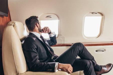 Photo pour Vue arrière de l'homme d'affaires en costume regardant par la fenêtre dans l'avion privé - image libre de droit