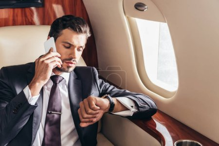 handsome businessman in suit talking on smartphone and looking at wristwatch in private plane