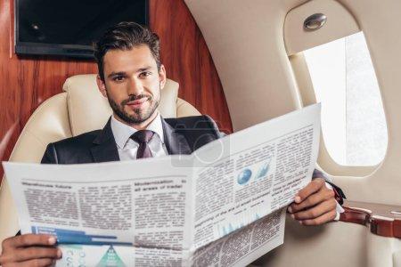 Photo pour Bel homme d'affaires en costume tenant journal dans un avion privé - image libre de droit