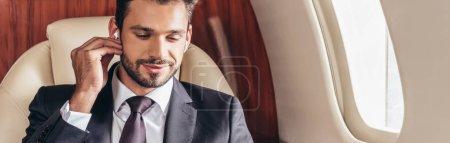 Photo pour Plan panoramique d'un bel homme d'affaires en costume écoutant de la musique en avion privé - image libre de droit