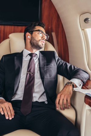 Photo for Handsome businessman in suit listening music in private plane - Royalty Free Image