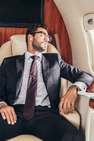 handsome businessman in suit sleeping and listening music in private plane