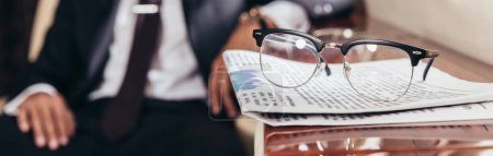 Photo pour Plan panoramique de lunettes et de journaux sur table en avion privé - image libre de droit