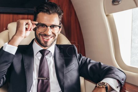 Photo pour Bel homme d'affaires en lunettes souriant et regardant la caméra dans un avion privé - image libre de droit